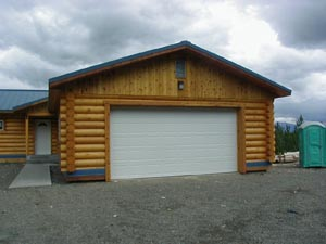 "10"" log-sided, saddle cornered oversized garage attached to pre-cut 10"" log home."