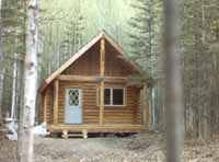 """This modified 16' X 20' Cheechako cabin is located at a remote Alaskan lake & was built by the owners & their friends. Our 8"""" Superior Logs assembled quickly & the wife called out the numbers & set the last log in place. What a way to go!"""