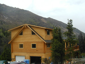 Log over frame garage with dormered loft.