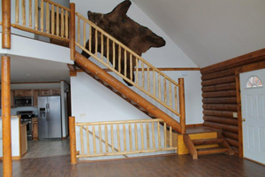 Great log stairs & rails - rail spindle by others-You know it's Alaska by the bear skin on the wall