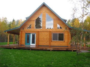"Front view of 8"" log home with 2 side covered decks.."