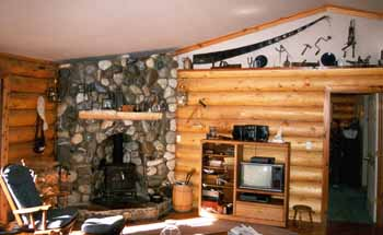 "This home has a river rock fireplace nestled into our 10"" Superior Logs wall on the left. The wall on the right is framed with our 10"" Superior Logs ""Authentic"" siding"