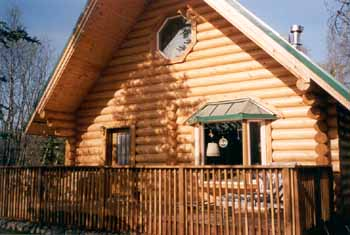 "The 26' X 32' Susitna plan in our 10"" Superior Logs was modified slightly for this Eagle River owner. The bay & octagon vinyl windows plus the 8' deck make this a cozy retreat. Our 10"" Superior Logs top 3 courses stagger to 4' carrying the roof overhang with the glue lam beam ridge. Our 10"" Superior Logs half log siding is on the front gable only with 1 X 6 T & G knotty pine on the back. The Susitna 26' X 32' weathered-in shell package price is available in 8"" & 10"" Superior Logs."