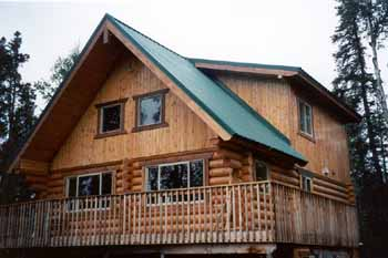 "The 26' X 32' Sleeping Lady plan in our 10"" Superior Logs was modified to sit over a basement for this Anchorage Hillside owner. Our 10"" Superior Logs stagger to 4' carrying the roof overhang with the glue lam beam ridge. 1 X 6 T & G #2 knotty pine is above & below the logs. There is a view of Cook Inlet from the 1/2 loft master suite."