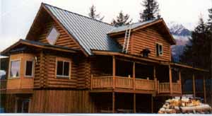 "The 28' X 40' McCarthy plan in our 10"" Superior Logs was modified to sit over a basement for this Seward home owner. Our 10"" Superior Logs half log siding is on both gable dormers & gable ends. One side has saddle corners & the other post butting corners. The 10' X 14' formal dining/sunroom with bay window has an 8' log arch entry. Wrap around decks with our log post supports offer a great seat for their mountain views. The 2 X 8 frame basement adds an additional 1,260 sq. ft. to the home. We provided the weathered-in shell package for the owner builder. We have the 28' X 40' McCarthy 2 upper floors weathered-in shell package price available in both 8"" & 10"" Superior Logs."