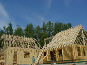 """Pre-cut 8"""" Superior Logs with attached frame garage that will be log-sided to match the home."""