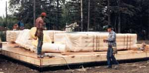 """Our pre-cut Alaskan made Superior Logs are shipped in bundles weighing approx. 2,500 lb. or less. The bundles are clear poly wrapped, metal strapped with thick cardboard corners against the logs (no straps touch your logs) & """"X"""" braced on each end. We also use wood slats (stickers) between each course to stabilize the bundles so our packages can travel great distances. We delivered the 26' X 36' Juneau plan subfloor to the job earlier. When the subfloor was in place the logs arrived."""