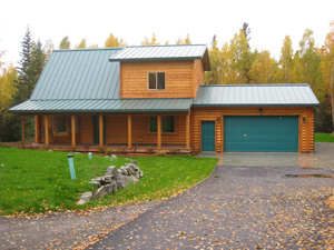 "Entry view of beautiful 8"" pre-cut Superior Logs home with oversize 2 car garage in our half log siding with saddle corners."