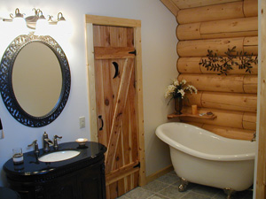 Country style bathroom. Behind outhouse style door  is pullchain toilet.