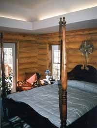 "This master bedroom suite has recessed lighting above our 10"" Superior Logs walls. We sometimes add an extra log wall course to make rooms feel more spacious without expanding the square footage. The wood bed truly accents the log look."