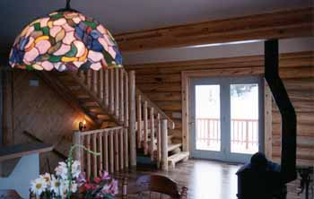 "This home has 10"" Superior Logs stair stringers & 10"" half log treads. The handrail was field built & hand fashioned from 3"" X 3"" rough sawn lumber & a half 6"" Superior Logs top rail we provided. The wood stove & laminate floor accent the log look. The owners have a beautiful mountain view"