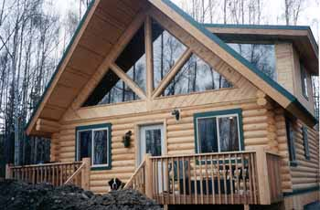 "The front of the ""Kenai Prince IV"" is guarded by our owner's Saint Bernard. The 1X6 T&G knotty pine reversed herring bone pattern is a nice touch on the gable. The prow front trap windows, dormers, 6' deck log rail posts make this home an extraordinary beauty gracing the Peters Creek country side."