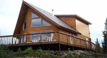 "The 28' X 32', 1,554 sq. ft. Eklutna plan in our 8"" Superior Logs overlooks the Kenai River with full wrap around 4' & 12' decks. The 6' frame prow front window wall has our 8"" Superior Logs half log siding on both sides. Our 1 X 6 T & G #2 knotty pine graces the 2 shed dormers with a the master suite with walk-in closet & full bath in the 1/2 loft. We provided the full weathered-in shell package for the owners. The Eklutna 28' X 32' (as shown) & 28' X 36' weathered-in shell package prices are available in 8"" & 10"" Superior Logs."