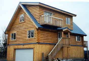 "The 26' X 40' modified Aleutian in our 10"" Superior Logs sit over an above ground 2 car garage with recreation room & storage. This Mat-Su Valley owner has mountain & Susitna River views from the front deck, great room & 1/2 loft master suite. Our 10"" Superior Logs half log siding covers the gable ends & dormer above the pre-cut logs. The steel roof puts the snow on the ground where it belongs. We provided the full weathered-in shell package for this owner builder. We have the 26' X 40' Aleutian 2 upper floors weathered-in shell package price available in both 8"" & 10"" Superior Logs."